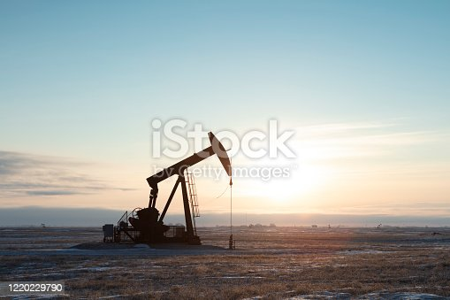 Single pump jack producing oil, sun rising. Image taken from a tripod.