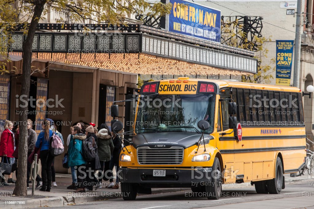 North American Yellow School Bus parked on a street, waiting for students to go out in a downtown area of Toronto, Ontario, Canada Picture of a School Bus, abiding by the rules of North America Traffic and Transportation, parked on a street in Downtown Toronto, the main city of Ontario and of Canada, with students standing in front Bus Stock Photo