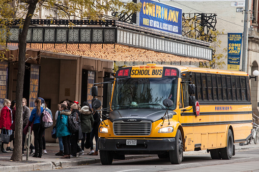 North American Yellow School Bus Parked On A Street Waiting For Students To Go Out In A Downtown Area Of Toronto Ontario Canada Stock Photo - Download Image Now