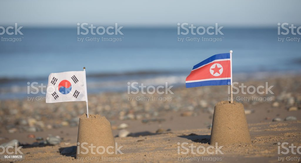 North and South Korean flags on beautiful beach stock photo