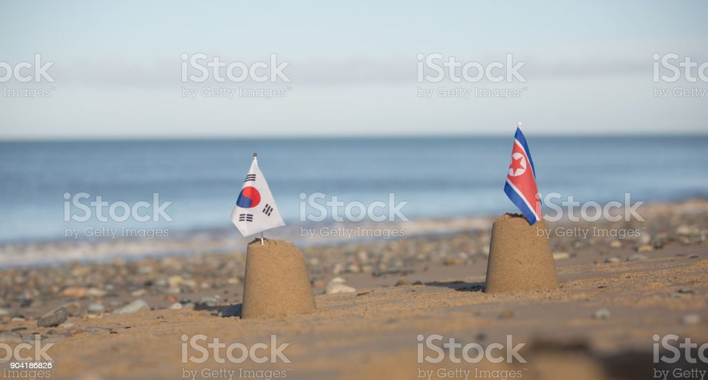 North and South Korean folded flags on beautiful beach stock photo
