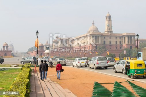 New Delhi, India - February 5, 2014: People and vehicles on the street outside North Block buildings, which houses the offices of the Federal Home and Finance Ministries in New Delhi, India. The North and South Blocks, and the President's House known as Rashtrapati Bhavan in the background, were built by the British when they ruled India.