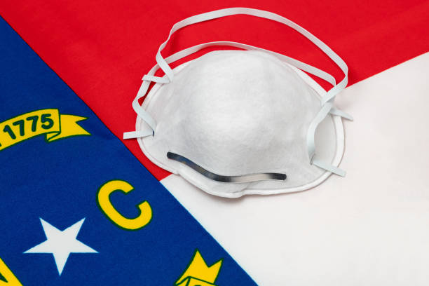 North Carolina state flag and N95 face mask. Concept of state and local government face covering mandate, order, requirement and social distancing during Covid-19 coronavirus pandemic stock photo