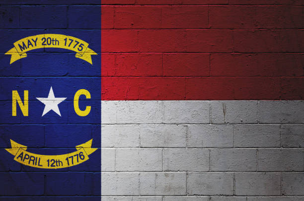 North Carolina state flag painted on a wall Flag of the North Carolina painted on a brick wall. north carolina us state stock pictures, royalty-free photos & images