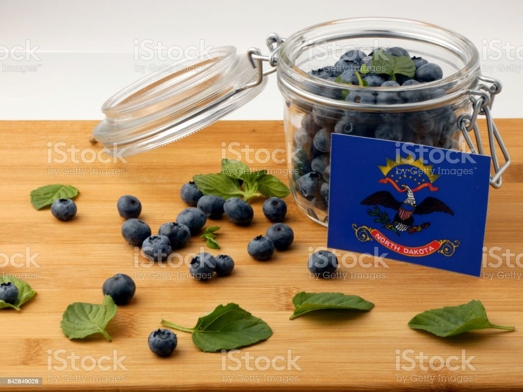 North Dakota flag on a wooden plank with blueberries isolated on white stock photo
