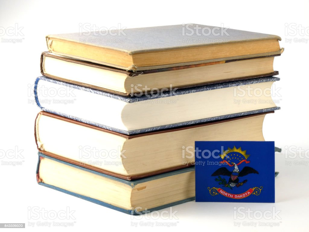 North Dakota flag with pile of books isolated on white background stock photo