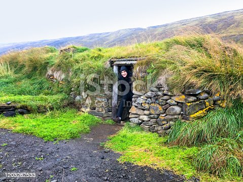 North Iceland: Tall man ducking out of a roadside vintage turf home. Shot Near Seydisfjordur.