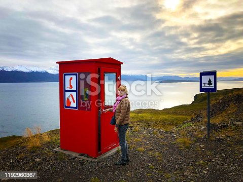 North Iceland: Active senior woman at a red phone booth at the edge of a fjord in North Iceland, with snowcapped mountains in the background. The photo was shot on Troll Peninsula (Trollaskagi) near the village of Siglufjordur.