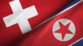 North Korea and Switzerland two flags together textile cloth, fabric texture