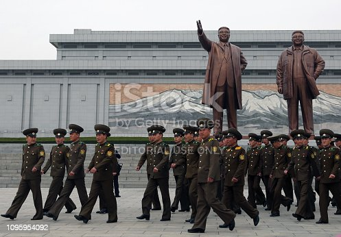 April 13, 2018. Mansudae Grand Monument, Pyongyang, North Korea. Soldiers visiting the huge statues of North Korean leaders.  Kim Il-Sung and Kim Jong-Il have special posters and monuments in different parts of the city. The most important of these monuments is the giant sculptures of North Korea's founding leader Kim Il-Sung and his son Kim Jong-Il. All tourists who come to visit the country have to come here and show their respects.