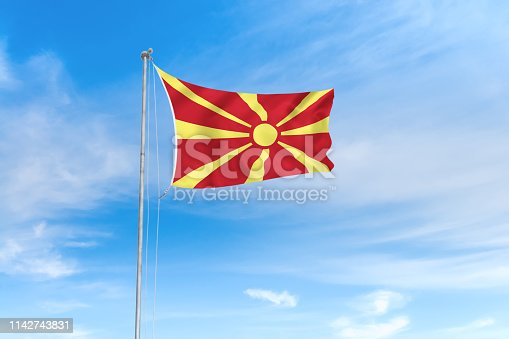 1056280906istockphoto North Macedonia flag over blue sky background 1142743831