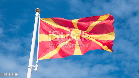 686175420 istock photo North macedonia flag waving in sunny blue sky. 1154844169