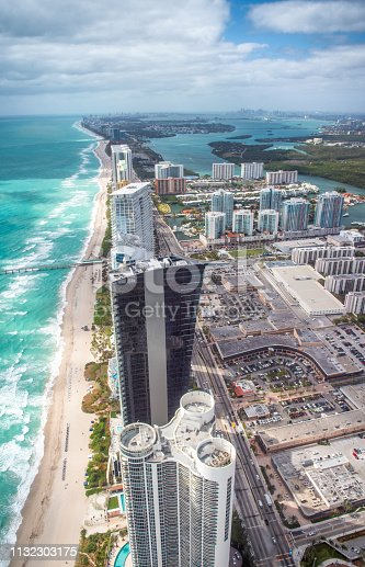 North Miami Beach as seen from helicopter. Skyscrapers along the ocean, aerial view.