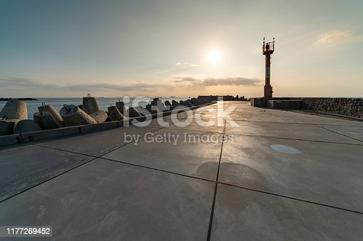 North pier with breakwaters, sunset seascape. Modern lighthouse in sunlight. Tetrapods along edges of pier. Beautiful evening seascape.