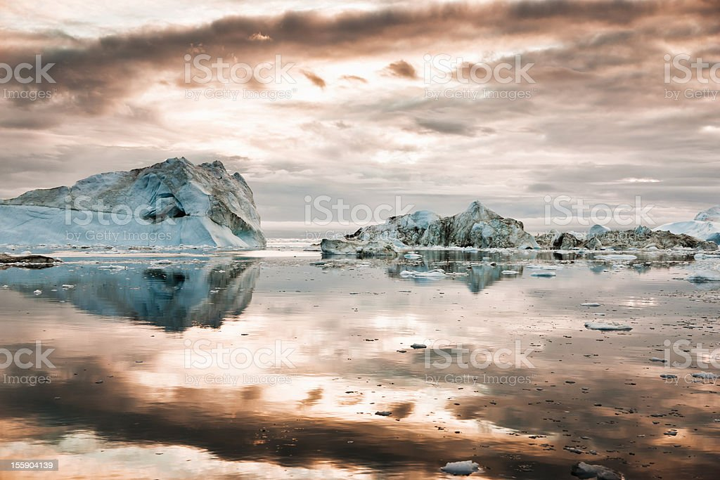North Pole Icebergs Arctic Greenland during Sunrise Sun rising over huge Icebergs in polar arctic icefjord at the west greenland coast. Ilulissat Icefjord, Greenland, North West Coast. Arctic Stock Photo