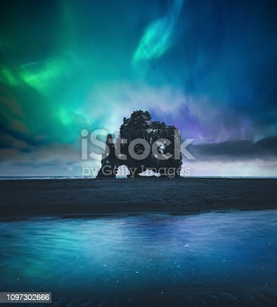 Northen lights over Hvitserkur rock formation at the beach (Vatnsnes peninsula, northwest Iceland).