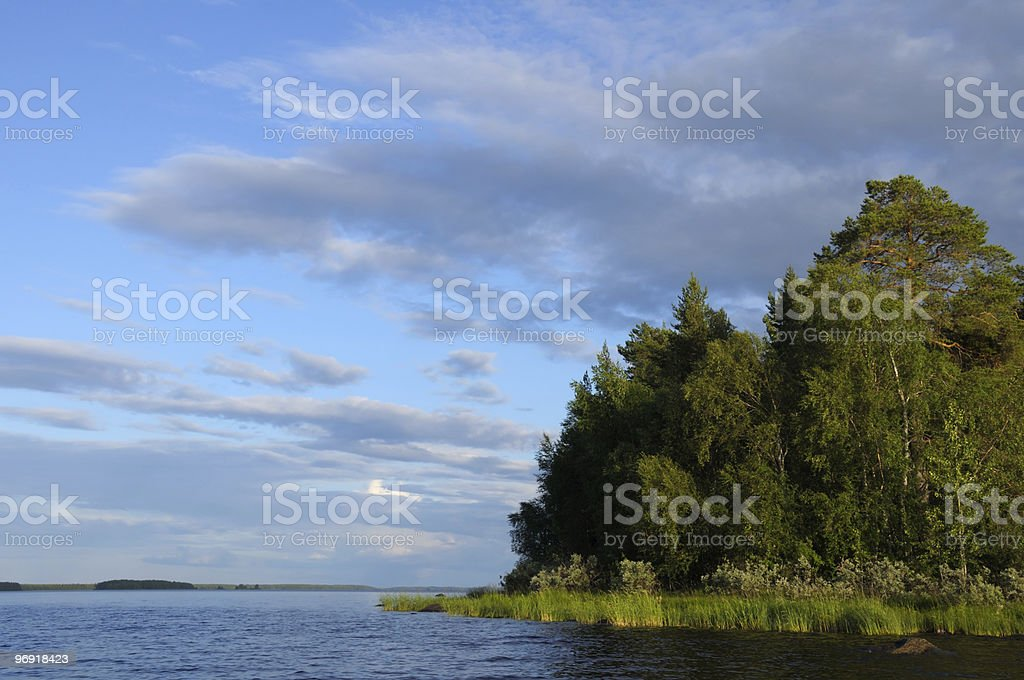 Northern forest islands in a huge lake royalty-free stock photo