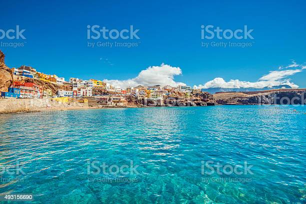 Cristall clear water and unspoiled canarian landscape at the beautiful fishing village of Sardina del Norte with its colorful houses.