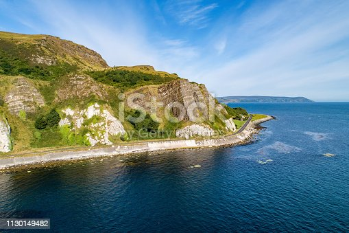 Northern Ireland, UK. Atlantic coast. Cliffs and A2 Antrim Coast Road, a.k.a. Giants Causeway Coastal Route. One of the most scenic coastal roads in Europe. Aerial view near Garron Point