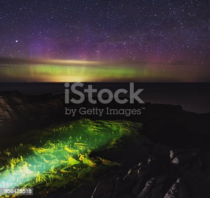 Northern lights shimmer above a small tidal lagoon on the Bay of Fundy coast.  Long exposure.