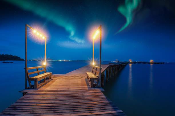 norrsken och natt himmel över trä bron på stranden - norrbotten bildbanksfoton och bilder