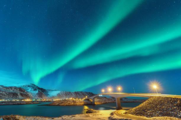 Nordlicht über Brücke mit Beleuchtung in Lofoten Inseln, Norwegen. Aurora Borealis. Sternenhimmel mit Polarlicht. Nacht Winterlandschaft mit Aurora, Straße, Dorf und schneebedeckten Bergen. Reisen – Foto