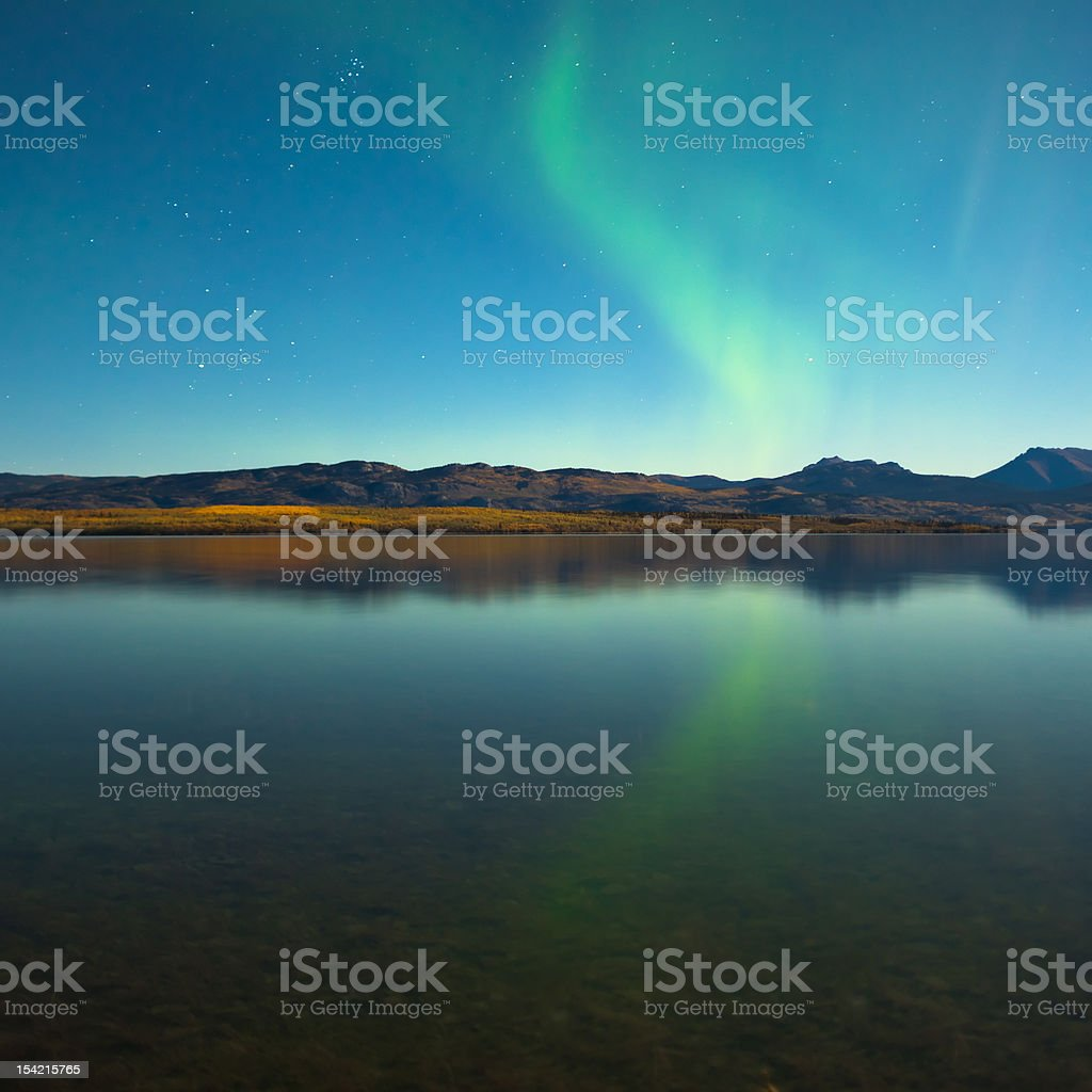 Northern lights and fall colors at calm lake stock photo