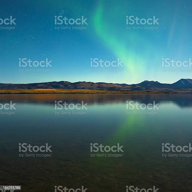 Photo of Northern lights and fall colors at calm lake