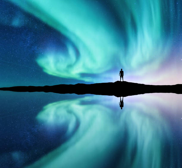 northern lights and silhouette of standing man in the hill in norway. aurora borealis and man. stars and green polar lights. night landscape with aurora, lake, sky reflection in water. travel. concept - aurora boreale foto e immagini stock