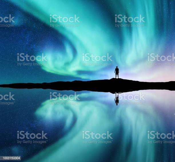 Photo of Northern lights and silhouette of standing man in the hill in Norway. Aurora borealis and man. Stars and green polar lights. Night landscape with aurora, lake, sky reflection in water. Travel. Concept