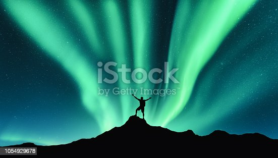 istock Northern lights and silhouette of standing man with raised up arms on the mountain in Norway. Aurora borealis and happy man. Sky with stars and green polar lights. Night landscape with aurora. Concept 1054929678