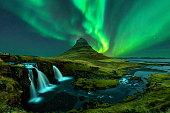 northern lights appear over Mount Kirkjufell with kirkjufellfoss waterfall in Iceland.
