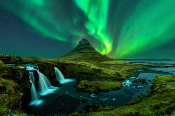nordlichter erscheinen über dem berg kirkjufell mit dem kirkjufellfoss-wasserfall in island. - iceland stock-fotos und bilder