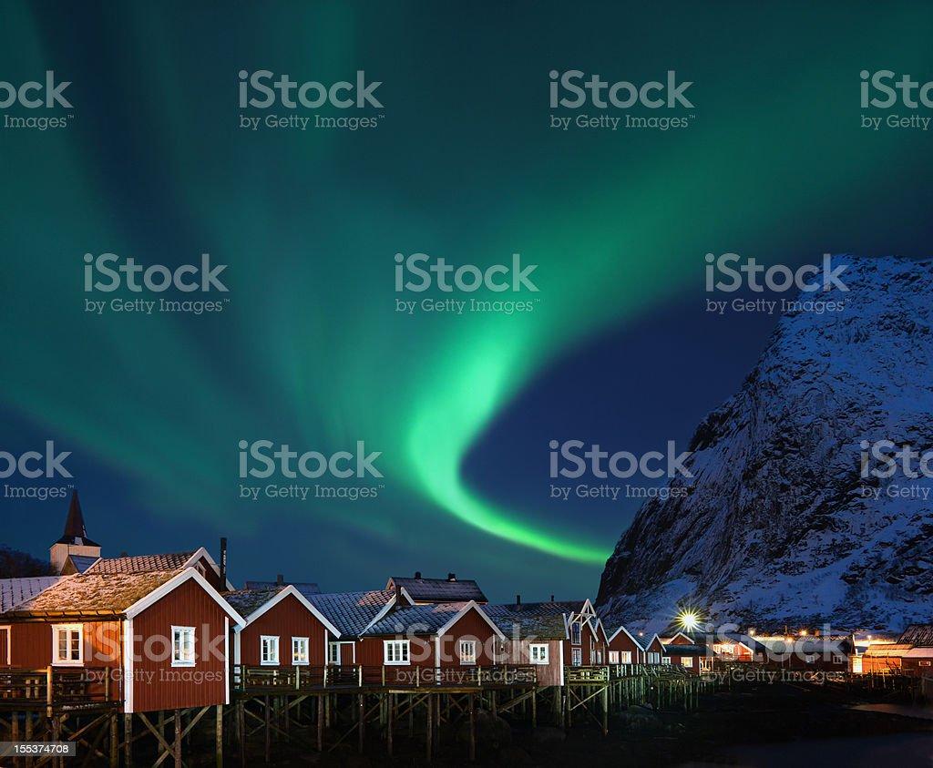 Northern lights - Aurora borealis over Reine, Lofoten, Norway Lovely shape of Northern lights (Aurora borealis) over traditional norwegian fishing lodges (rorbuer) and snowy mountain.  Aurora Borealis Stock Photo
