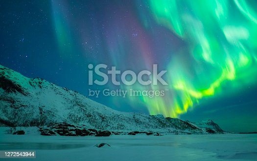 Northern Lights, polar light or Aurora Borealis in the night sky over the Lofoten islands in Northern Norway. Clear beam raising up behind  the high snow and ice covered peaks in the distance.