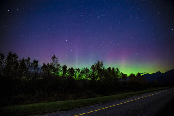 Northern Lights behind an empty road stock photo