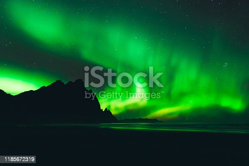 View of beautiful bright Aurora borealis with green, yellow and purple colors at the Stokksnes beach with Mountain View in East iceland