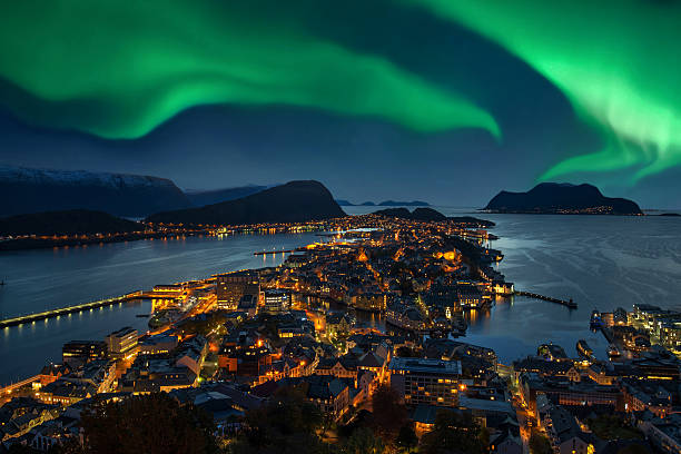 northern lights - green aurora borealis over alesund, norway - noorwegen stockfoto's en -beelden