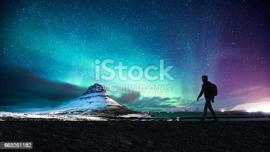Solo traveler walking in front of an awesome Northern Lights in Mount Kirkjufell Iceland.
