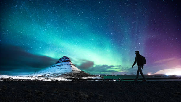 northern lights in mount kirkjufell iceland with a man passing by - aurora boreale foto e immagini stock