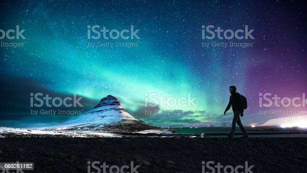 Photo of Northern lights in Mount Kirkjufell Iceland with a man passing by