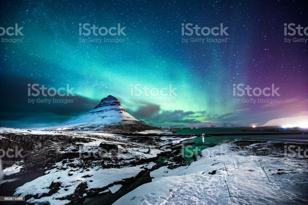 Northern lights in Mount Kirkjufell Iceland with a man passing by
