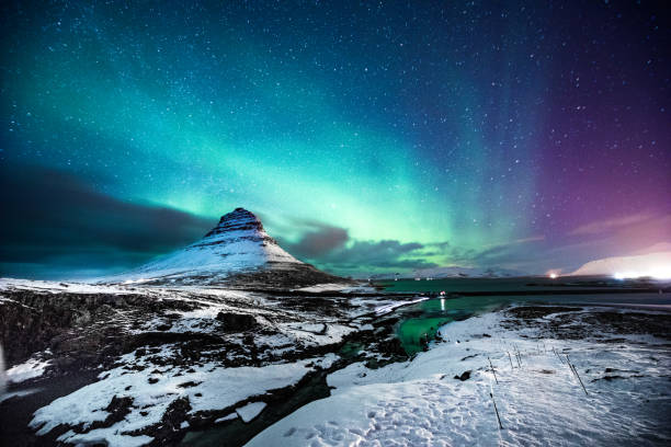 Northern lights in Mount Kirkjufell Iceland with a man passing by stock photo