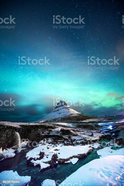 Northern lights in mount kirkjufell iceland with a man passing by picture id663878444?b=1&k=6&m=663878444&s=612x612&h=r57uapikgqzafenl  wtywpfaquqt1jcqnfe6w3r6xg=