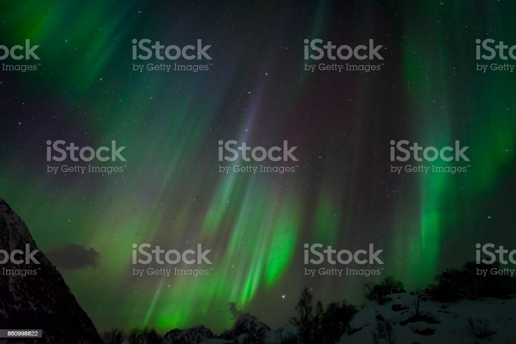 Northern Lights in the night sky over the Lofoten Islands in Norway stock photo