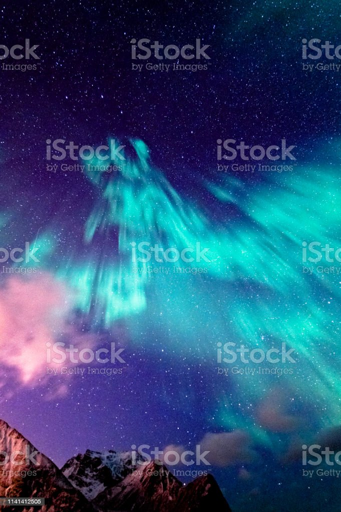 Northern Lights in Unstad Northern lights spotted in Unstad, Lofted in a cloudy sky. Arctic Stock Photo