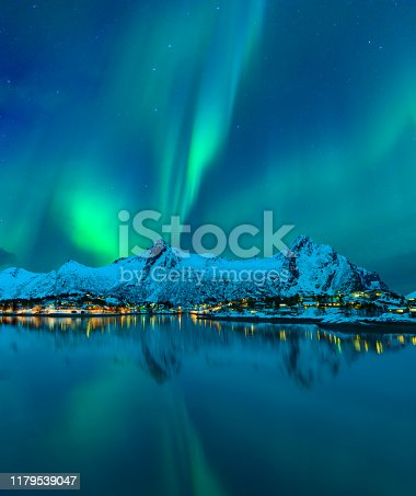 Northern Lights, polar light or Aurora Borealis in the night sky over the town of Svolvaer in the Lofoten in Norway with a reflection in the fjord in the foreground. The mountains in the background are covered in snow and ice.