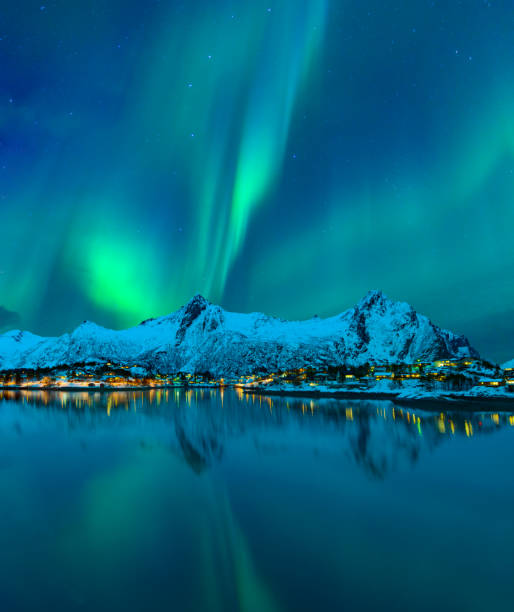 Northern Lights or Aurora Borealis in the night sky over the town of Svolvaer in the Lofoten stock photo