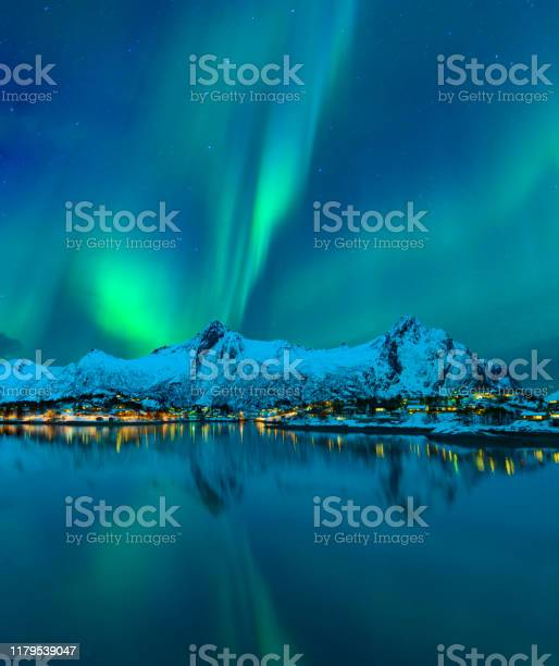 Photo of Northern Lights or Aurora Borealis in the night sky over the town of Svolvaer in the Lofoten