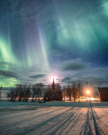 Northern lights over Christian church with the moon in winter at Flakstad, Norway
